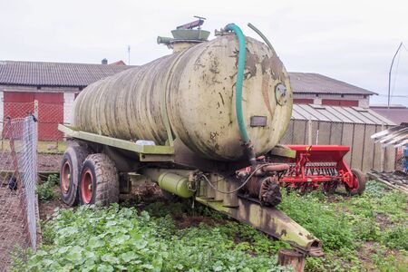 Tank for various liquids on a dairy farm. Barn and seeder in the background. .Side view. Podlasie, Poland.