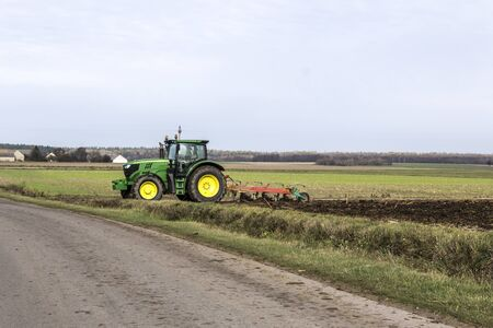 Wheel tractor with a plow, leaves the field on an asphalt road. Plowing the land in late autumn. Podlasie, Poland.