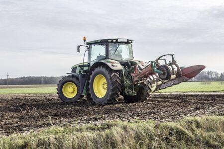 Tractor de ruedas con arado levantado, llamadas en el campo. Arando la tierra a finales de otoño. Podlasie, Polonia. Foto de archivo