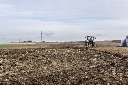 Wheel tractor with multi-plow. Plowing the land in late autumn. Podlasie, Poland.