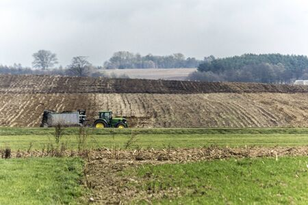 A  tractor with a trailer for spreading manure travels through a  field. Autumn work at a dairy farm. Podlasie, Poland.