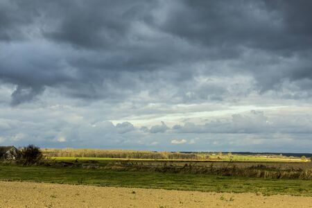Late autumn. Green grass  and brown arable land. Dark sky in the background. Dairy farm. Podlasie, Poland.