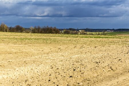 Late autumn. Large plowed field.  Meadows  and village in the background.  Dairy farm. Podlasie, Poland.
