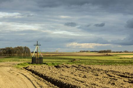 Late autumn.Metal cross standing at the crossroads. Old Christian tradition. Podlasie, Poland.