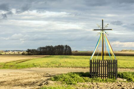 Late autumn. A cross standing at the crossroads, among fields and meadows.  Close-up. Old Christian tradition. Podlasie, Poland.