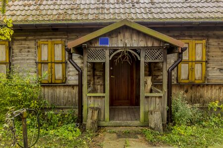 Late fall . The wooden porch of an old rustic wooden house. Wooden siding and patterns, shutters made of boards, tiled roof. Podlasie, Poland.