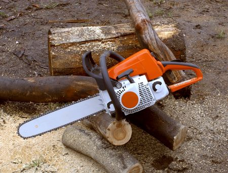 chainsaw used to cut up timber logs into firewood Foto de archivo