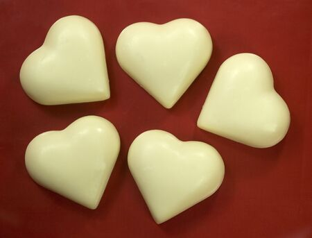 natural soap shaped as hearts on a red background photo