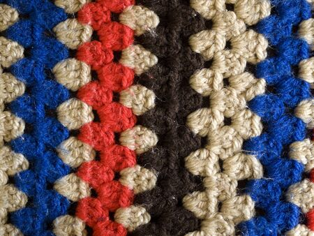 rug texture: synthetic woollen knitted crochet rug closeup texture red white blue brown background Stock Photo
