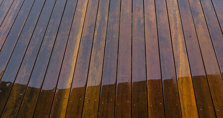 floorboards: Timber floorboards on outside deck wet from rain water for background Stock Photo