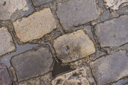 cobblestone road: Water puddles from rain on wet cobblestone road Stock Photo