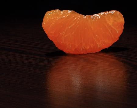 segmento: Un segmento di mandarino pelato su un tavolo di legno scuro