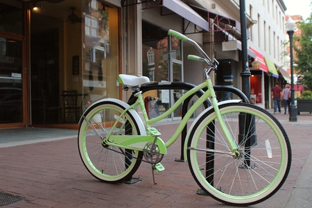 Light green bicycle beside the street on a sidewalk in the shopping district of a charming town. Reklamní fotografie