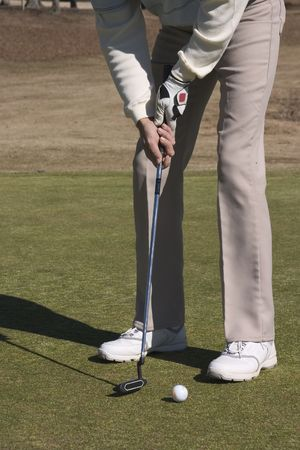 Male Golfer addressing the ball for a putt