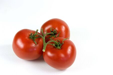 Three isolated fresh tomatoes with vine attached