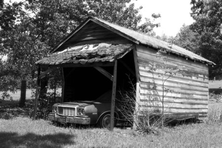 An old car sits abandon in a ramshackled old shed