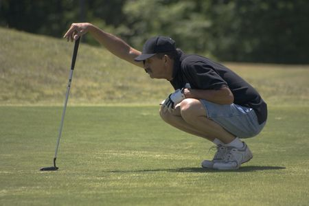 Male golfer reading the green for his putt