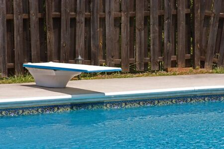 Diving board and cool water surrounded by a privacy fence just waiting for summertime fun Фото со стока