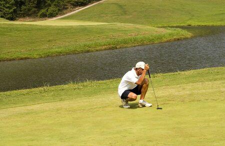 judging: Senior golfer judging the putting green