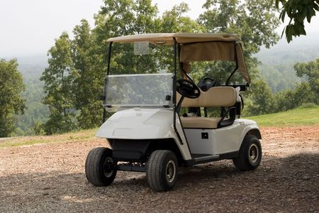 in readiness: A single new golf cart standing in readiness at a mountain top golf course Stock Photo