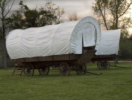 close up of a pair of conestoga wagons without animals