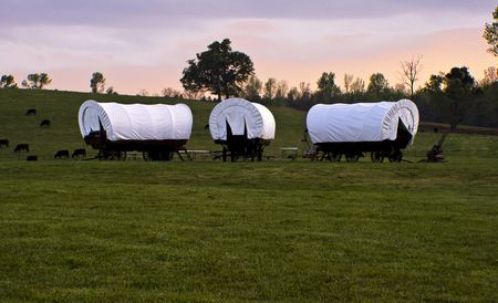 covered wagon: Conestoga wagons making camp in a field at sunset
