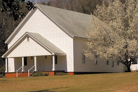 Plain rural church in the South with blooming cherry tree on the side photo