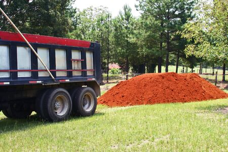 recently: Large dumptruck moving away from a recently dumped pile of top soil