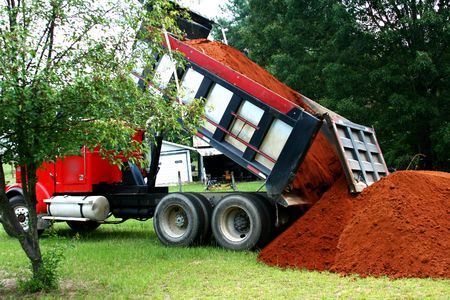 dumping: Large dump truck dumping a load of top soil in a grass yard Stock Photo