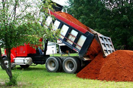 basurero: Las grandes cami�n volquete de dumping una carga de arriba del suelo en un patio de c�sped