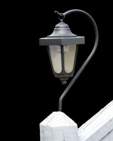 Single solar lamp on porch rail isolated over black