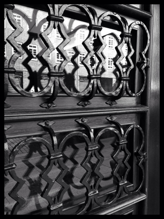 grate: Reflected windows in a window cover by wrought-iron grate