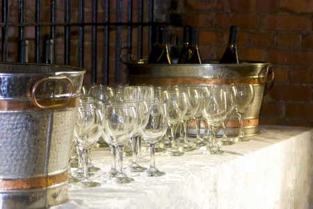 winetasting: Wine glasses sit beside iced wine bottles at a reception.