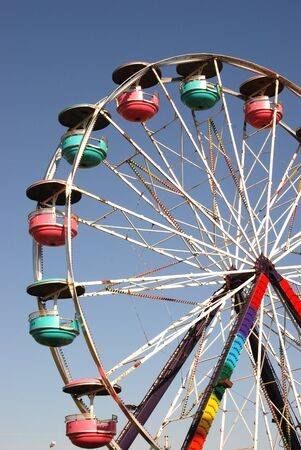 Colorful Ferris wheel spins against a clear blue sky.