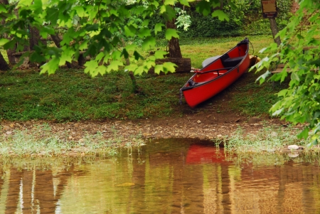 A red canoe waits by a river in rural Tennessee.
