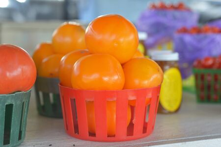 roadside stand: Basket of orange tomatoes for sale at a roadside fruit and vegetable stand