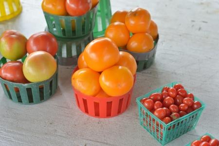 Baskets of different tomatoes for sale at a roadside fruit and vegetable market. Reklamní fotografie