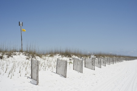 warns: A yellow caution flag warns swimmers at a beach near Pensacola, Florida. Stock Photo