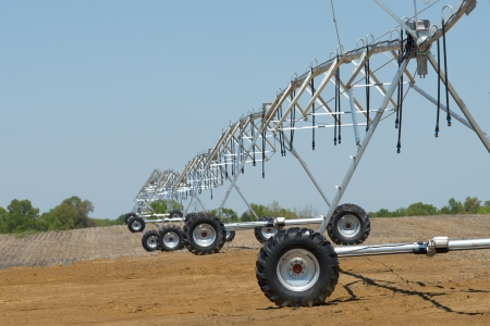 Irrigation equipment awaits the emergence of new plants  in a rural farm field