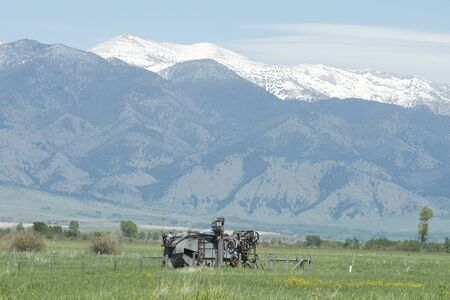 Antique farm combine sits in rural field in Montana with Mount Ellis in background