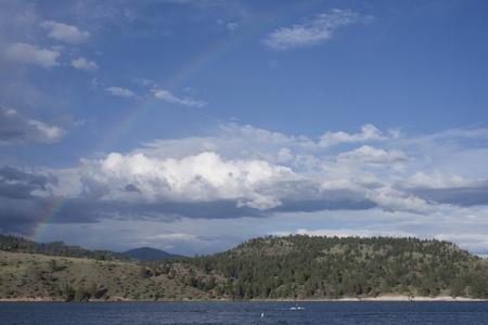 jet skier: Rainbow over jet skier at Hauser Lake near Helena, Montana.