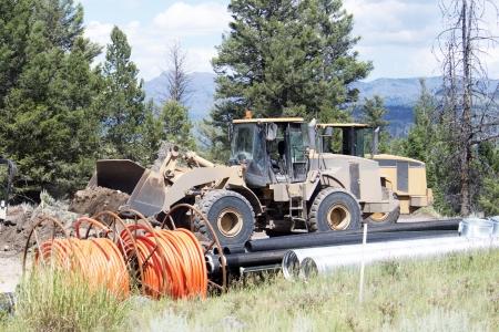 fibra óptica: Los trabajadores ponen el cable de fibra óptica junto a una carretera en las montañas rocosas.
