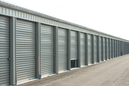 Storage units at a storage facility with one door parially open.