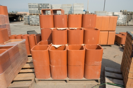 flue: Clay chimney flue liners for sale on a wooden pallet.