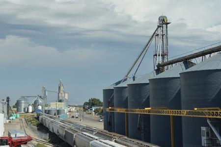 Grain storage silos beside a railroad track in a rural midwetern town. Editorial