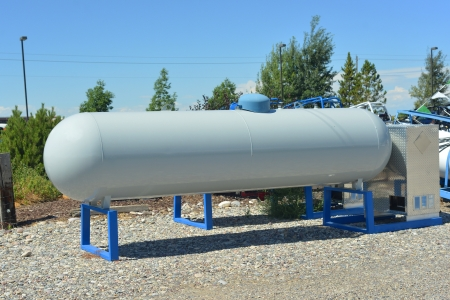 Large white portable propane tank stores pressurized fuel.