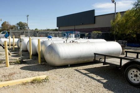 Propane tanks wait for transport beside a flatbed trailer. Stock Photo