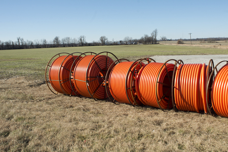power cables: Fiber optic cable ready to be laid in a rural area with an old barn