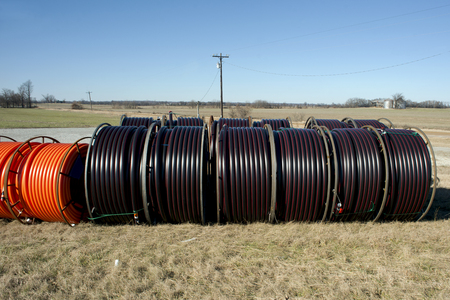 Fiber optic cable ready to be laid in a rural area with an old barn