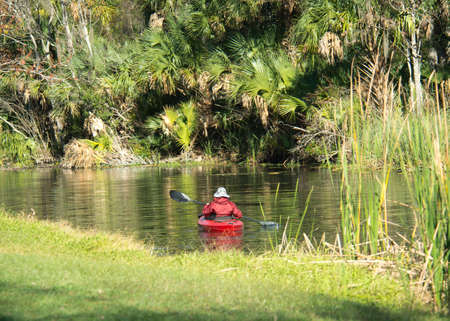 Kayaker paddles down a river in central Florida in winter